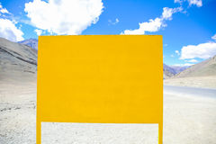Empty yellow signboard in mountain background - with copy space Royalty Free Stock Image
