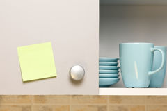Empty yellow sticker on cabinet door. Empty yellow sticker on kitchen cabinet door with some dishes Royalty Free Stock Image
