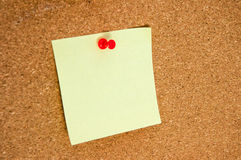 Empty yellow sticker for notes on the cork board close-up stock photography