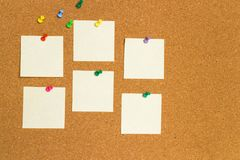Empty yellow sticky notes on cork board with color pins. Blank yellow sticky notes attached to cork board with color pins Stock Image