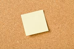 Empty yellow sticky paper memo note on cork board. With copy space royalty free stock image