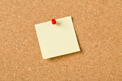 Empty yellow sticky paper memo note with red pin on cork board. With copy space royalty free stock images
