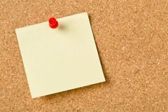 Empty yellow sticky paper memo note with red pin on cork board. With copy space stock image