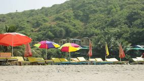 Empty yellow sun loungers under multi-colored beach umbrellas on the wind on the yellow sand against the background of a green mou