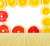 Empty yellow wooden deck table with fresh grapefruit and oranges rings set isolated on white background with copy space. Ready fo Royalty Free Stock Image