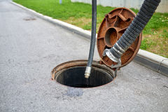 Emptying septic tank, cleaning the sewers. Septic cleaning and sewage removal. Emptying household septic tank. Cleaning sludge from septic system Royalty Free Stock Photos