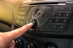 Empujando el botón de encendido manualmente para girar el coche estéreo Imágenes de archivo libres de regalías