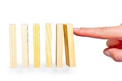 Empujando la fila manualmente de los dominós alineados imagen de archivo