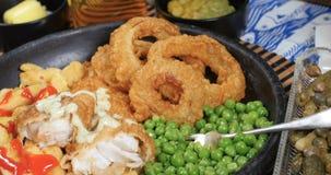 Empujar del carro hacia adentro del enfoque la opinión hacia fuera del pescado frito con patatas fritas ingleses almacen de video