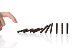 Empujar dominós manualmente Imágenes de archivo libres de regalías