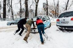 Empujar el coche en nieve, Bucarest, Rumania Imagen de archivo