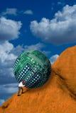 Empujar la bola del ordenador encima de la colina Foto de archivo libre de regalías