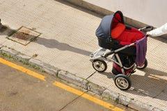 Empujar un cochecito de niño manualmente Foto de archivo libre de regalías