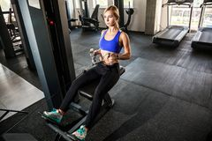 Empuje en simulador del bloque Entrenamiento atlético de la mujer en gimnasio imagenes de archivo