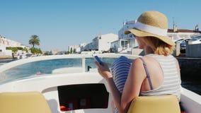 Empuriabrava, Spanje: Jonge toerist met een hoed die op een boot op het kanaal drijven, die een mobiele telefoon met behulp van C stock footage