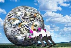 Empurrando a bola do dinheiro Imagens de Stock