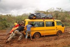 Empurrando o carro fora da lama Fotos de Stock Royalty Free