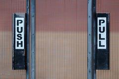 Empurre e puxe sinais na porta Imagens de Stock