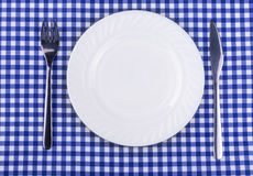 Empy plate and with a knife fork on the tablecloth in a cage Stock Photo