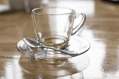 Empy tea cup on saucer and spoon. On wooden table Royalty Free Stock Photos
