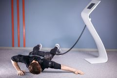 EMS male doing push ups in gym while connected to electric muscle stimulator. EMS male working out, doing push ups in gym while connected to electric muscle Stock Image