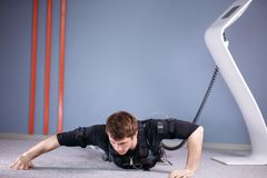 EMS male doing push ups in gym while connected to electric muscle stimulator. EMS male working out, doing push ups in gym wearing electric muscle stimulation Stock Photography