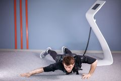 EMS male doing push ups in gym while connected to electric muscle stimulator. EMS male working out, doing push ups in gym wearing electric muscle stimulation Stock Images