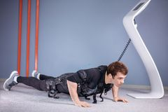EMS male doing push ups in gym while connected to electric muscle stimulator. EMS male working out, doing push ups in gym while connected to electric muscle Royalty Free Stock Photos