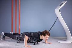EMS male doing push ups in gym while connected to electric muscle stimulator. EMS male working out, doing push ups in gym wearing electric muscle stimulation Royalty Free Stock Images