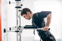 EMS male working out, doing push ups. man doing triceps dips on parallel bars. EMS male working out, doing push ups. Fit man doing triceps dips on parallel bars Royalty Free Stock Photos