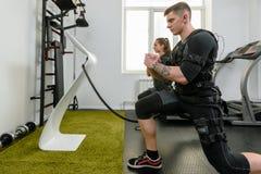 EMS que squatting no gym fotografia de stock