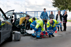 EMS teamwork. A team of emergency medical services at work, lifting an injured woman on a stretcher, to carry her away Royalty Free Stock Photo
