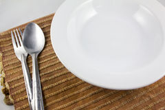 Emtpy dish near fork and spoon Stock Image