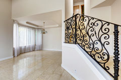 Emtpy house interior. Marble staircase with black wrought iron r Stock Images