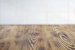 Emty clear aged brown wooden table for product placement . Kithen rustic rural table for food. White cblurred cell tile on the ba stock images