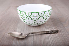 Emty decorated bowl and spoon Royalty Free Stock Image