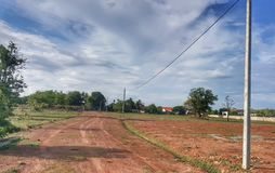 Emty land Ready for building a house under beautiful blue sky in Laos. The land with blue sky and electricity pole and few trees in Vientiane, Laos stock photos