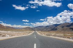 Emty road vanishing into HImalayas mountains in Ladakh. Northern India. Road trip concept stock images
