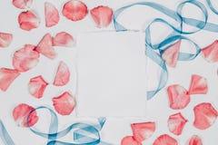 Emty tapezieren Blatt mit den rosa Blumenblättern und blauem Band Flache Lage, Draufsicht, copyspace Stockfotos