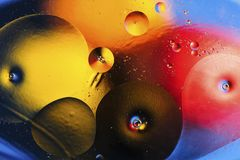 Color abstract background based on red, yellow, orange and brown circles and ovals. Emulsion of water and oil on a colored background. Beautiful color abstract Stock Photos