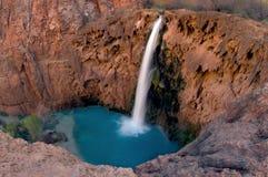 Enöga sikt av Havasu nedgångar betonar det kontrastera blåa gröna vattnet mot det craggy rött vaggar väggen som omger det arkivfoto
