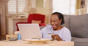En äldre afrikansk amerikankvinna använder hennes kreditkort och bärbar dator för att göra någon online-shopping Fotografering för Bildbyråer