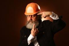 En äldre arbetare i tecken för gester för en hjälm varnande, studiostående arkivfoto