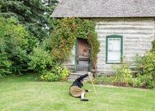 En äldre dam som är stupad ner på det gröna gräset framme av huset Arkivfoton