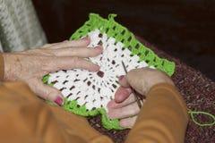 En äldre dam som gör virkning Arkivfoto