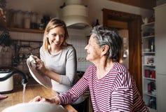 En äldre farmor med en hemmastadd vuxen sondotter och att tvätta disken royaltyfri foto
