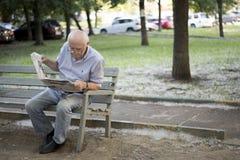 En äldre gråhårig man läser försiktigt en tidning, medan sitta på en bänk i, parkerar arkivfoton