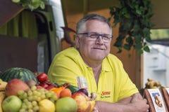 En äldre intressant man i exponeringsglasleenden som säljer fruktsmoot Arkivfoton