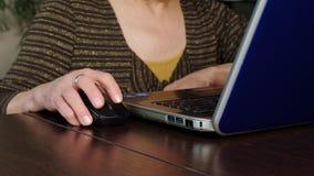 En äldre kvinna använder en bärbar dator hemma stock video