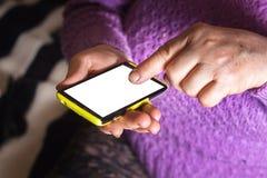 En äldre kvinna, en farmor som rymmer en smart telefon i handen, diameter fotografering för bildbyråer